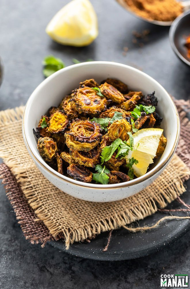 baked karela served in a white bowl, garnished with cilantro and lemon wedge