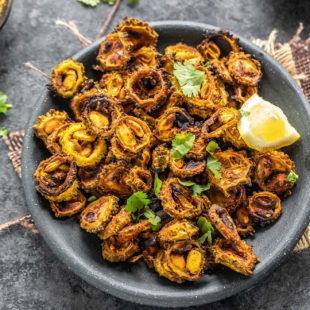 sliced karela with spices served in a black plate garnished with lemon wedge and cilantro