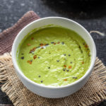 bowl of green color coconut chutney with few vadas placed in the background