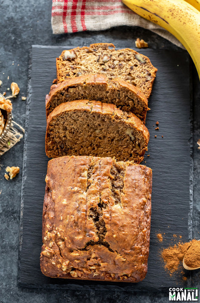a banana bread with three cut slices placed on a black board with a banana placed on the side