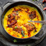 punjabi kadhi pakora served in a cast iron kadai with cilantro and broken red chilies scattered in the background