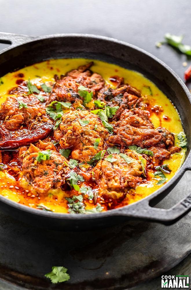 bowl of yellow kadhi with pakora in a iron kadai garnished with cilantro