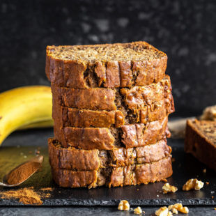 stack of banana bread slices placed on a black board with pieces of walnuts sprinkled around and a banana kept in the background