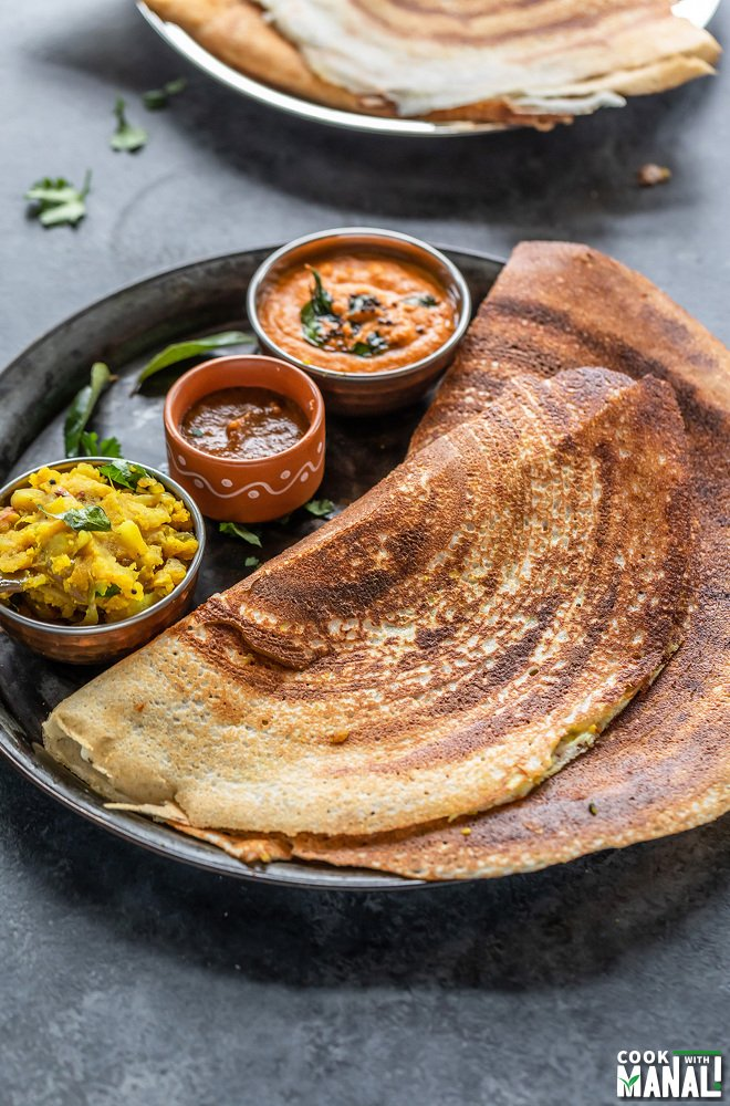 two dosa placed in a plate with bowls of chutneys and potato masala