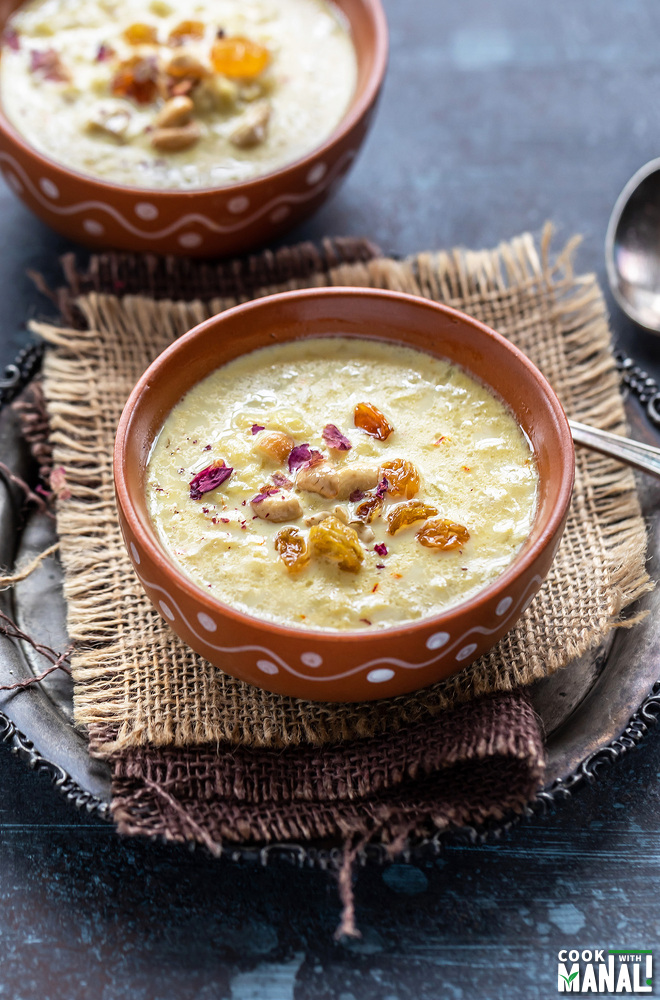 lauki kheer served in a clay bowl garnished with nuts, raisins and dried rose petals