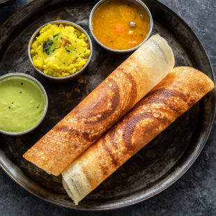 two crispy masala dosa rolled and placed in a round plate along with bowls of sambar, chutney and potato masala