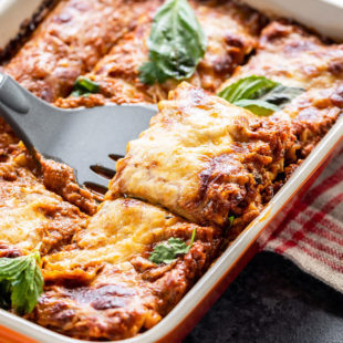 paneer lasagna in an orange color baking dish with a spatula scooping out a portion from the lasagna