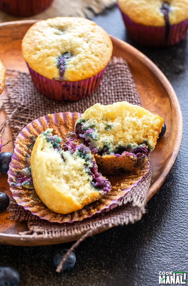two blueberry muffins placed on a wooden plate with one of them cut in half to show the texture of the muffins