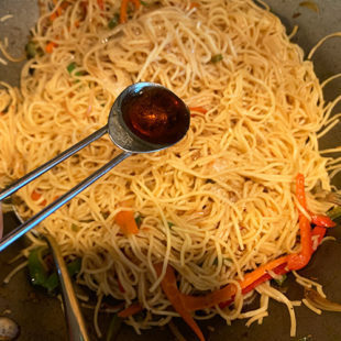 a teaspoon of sesame oil being added to a wok of noodles