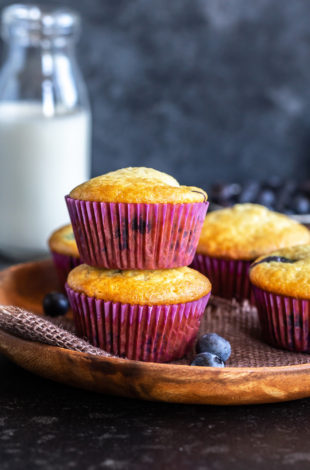 two muffins stacked on top of each other, with more muffins on the side and a bowl of blueberries and a bottle of milk in the background