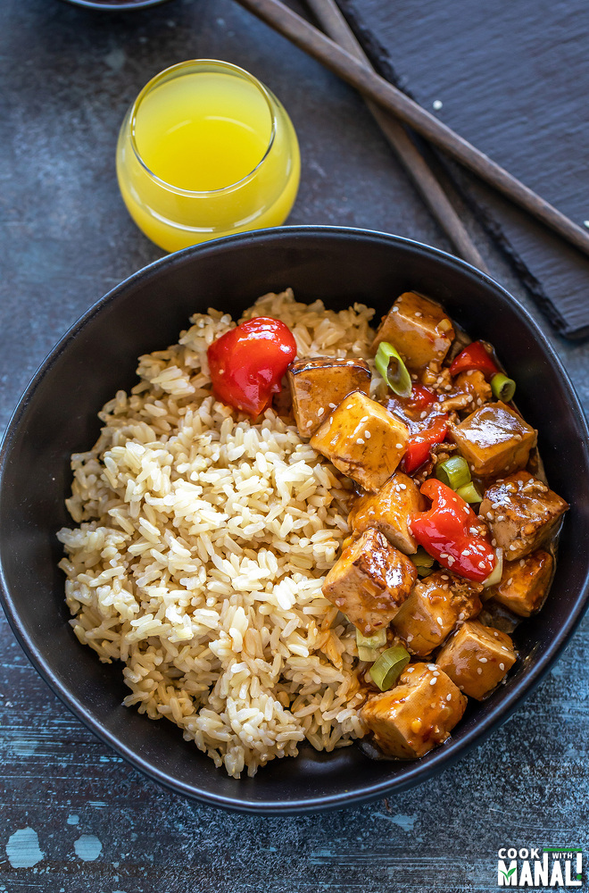bowl of tofu topped with sesame seeds and brown rice with a glass of pineapple juice in the background with a bowl of hot sauce placed on the side
