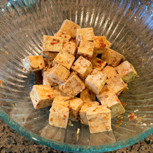 marinated tofu cubes in a glass bowl