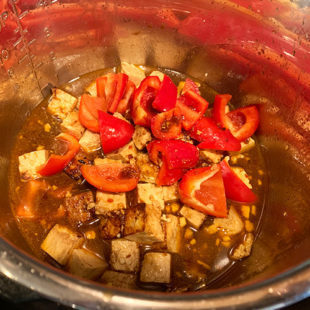 cubes of tofu with red bell peppers in brown color sauce