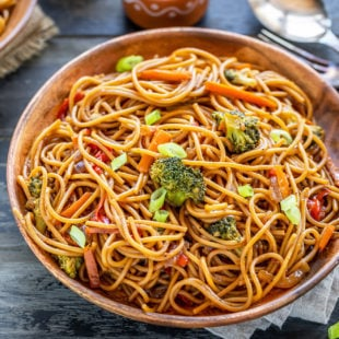 noodles with veggies served in a wooden plate with bowls of chili sauce and soy sauce placed in the background