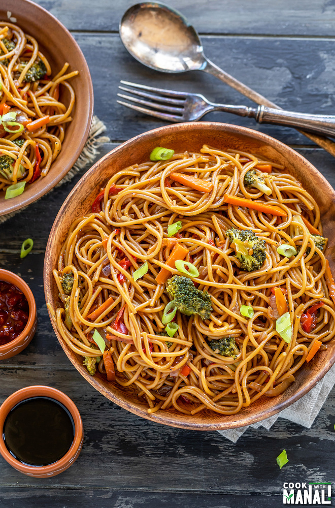 noodles with veggies served in a wooden plate with bowls of chili sauce and soy sauce placed on the side and another bowl of noodles in the background