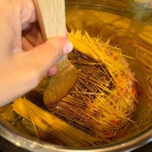 a wooden spatula pressing spaghetti noodles arranged in a criss-cross manner in an instant pot