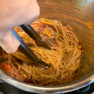 a pair of tongs holding spaghetti noodles in an instant pot