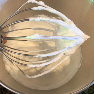 wire whisk attachment of stand mixer with whipped cream