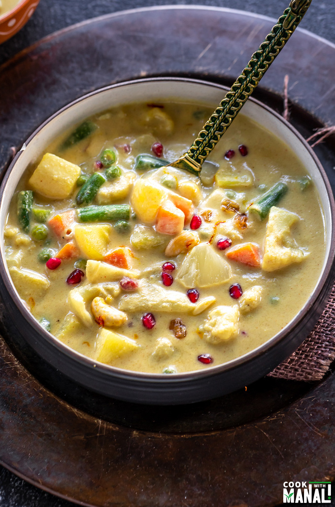 yellow color vegetable curry served in a bowl with a golden color spoon