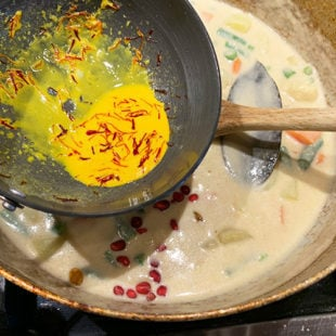 saffron milk (yellow in color) being added to a pan full of veggies in a white sauce