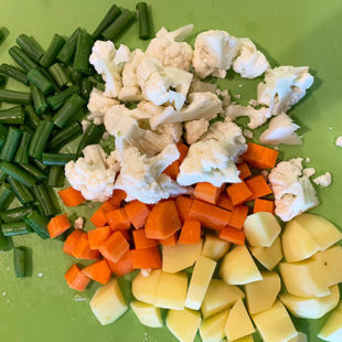 a green mat with chopped potato, cauliflower, beans, carrot placed on it