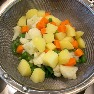 a colander with boiled potato, cauliflower, beans, carrot and peas