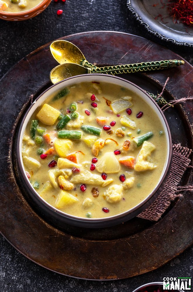 yellow color vegetable curry in a round bowl garnished with pomegranate arils and two golden color spoons placed in the background