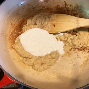 pan with white color paste and yogurt being added to it