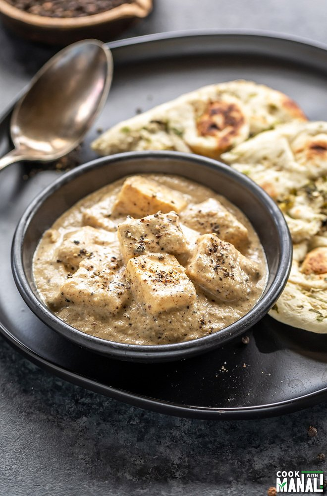 paneer cubes in a creamy white sauce served in a black bowl with pieces of naan placed in the background