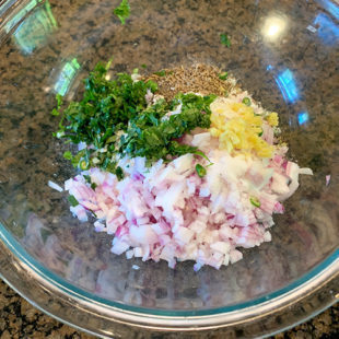 a bowl with some chopped onion, cilantro, ginger
