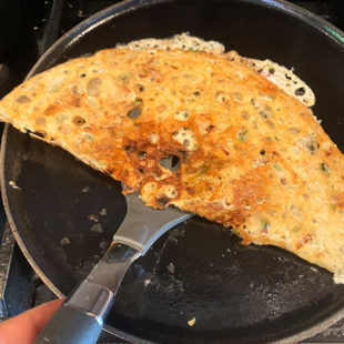 a dosa being folded in half by a spatula