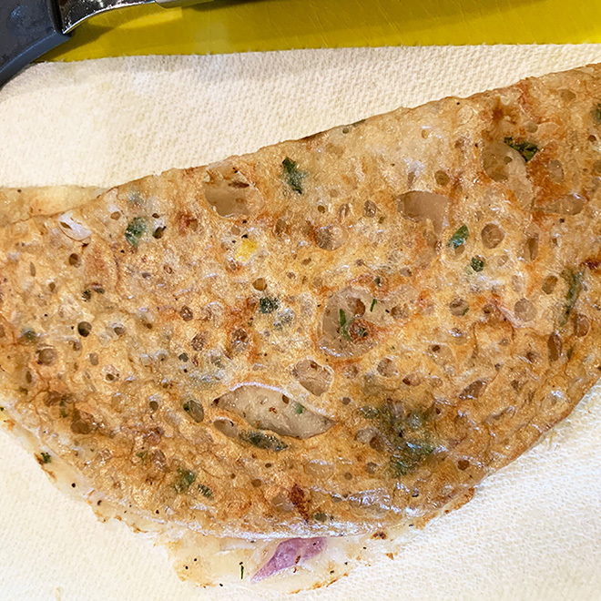 a dosa placed on a white kitchen towel