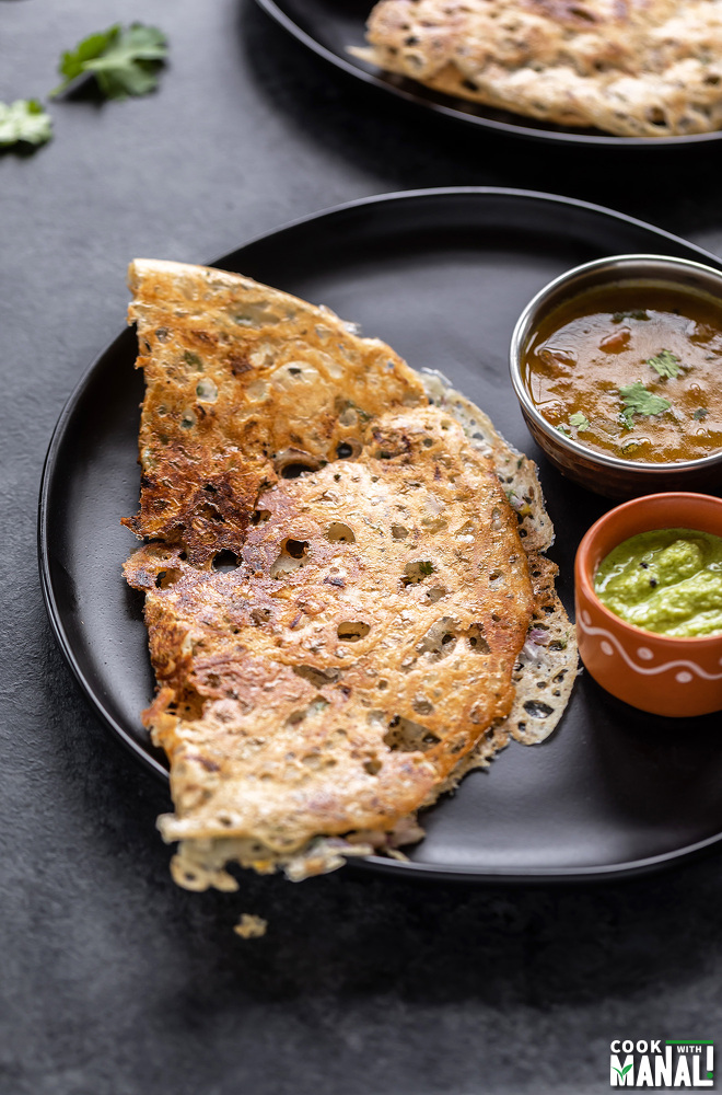 rava dosa placed in a black round plate with a bowl of sambar and a bowl of chutney