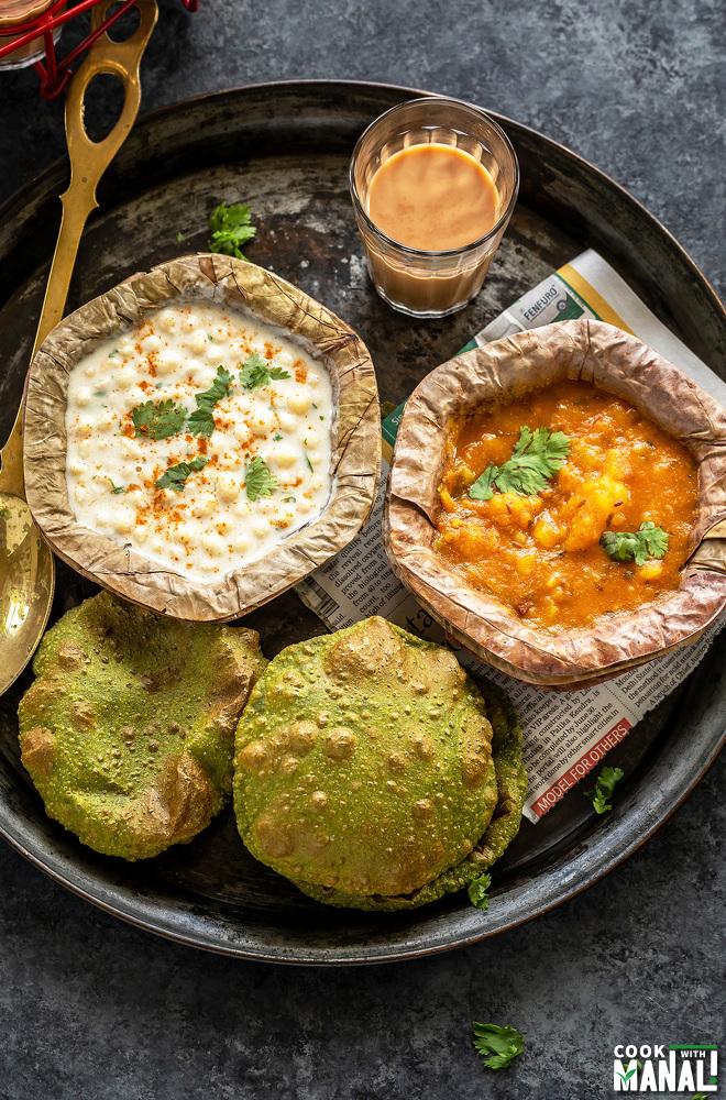 an Indian platter with puri, potato curry, glass of chai and boondi raita