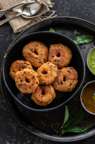 medu vada arranged in a black bowl with curry leaves placed on the side and spoons placed in the background