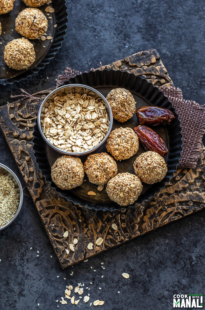 sesame oats balls placed in a plate with 2 medjool dates placed on one side and bowl of oats on the other side