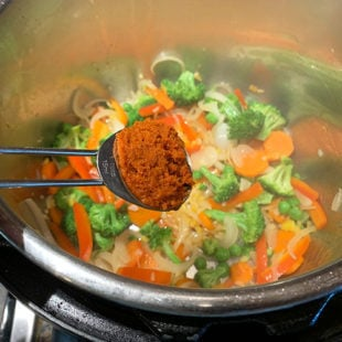 curry paste being added to a pot of veggies