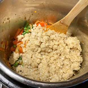 cooked quinoa being added to a pot