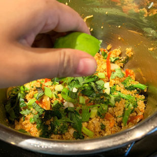 hand squeezing lime juice in a pot full of veggies and quinoa