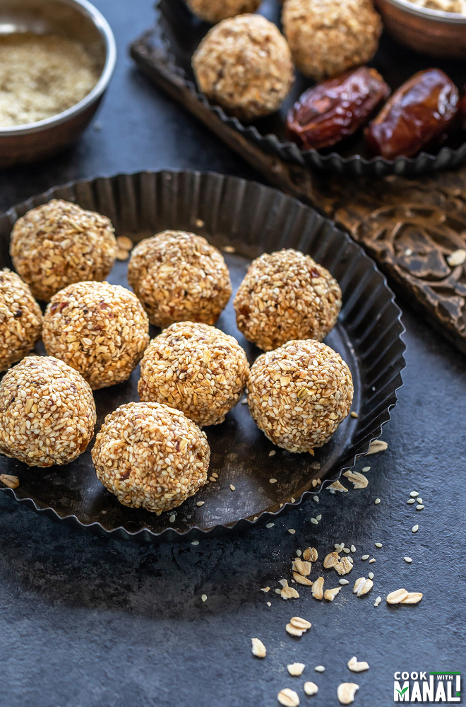 sesame oats ladoo (balls) placed in a rimmed black plate with some rolled oats scattered around and a bowl with sesame seeds in the background