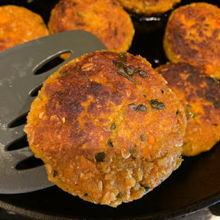 golden brown sweet potato tikki being taken out of a skillet using a spatula