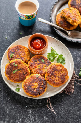 sweet pottao tikki arranged in a white plate with a small bowl of ketchup on the side a glass of chai placed in the background