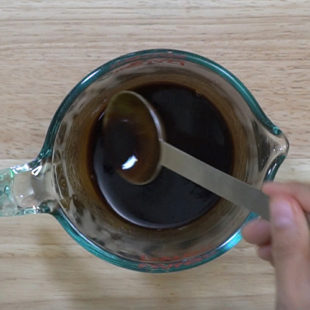measuring jar with soy sauce, tamarind concentrate being mixed together
