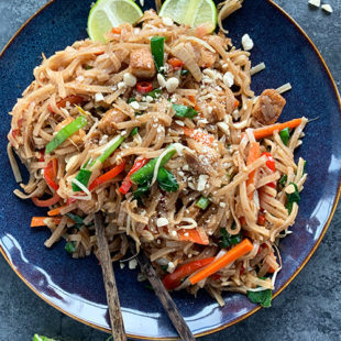 pad thai noodles served in a blue plate with pair of chopsticks