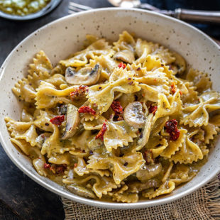 bowl of bow-tie pasta with mushrooms and sun-dried tomatoes