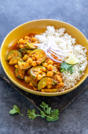 zucchini chickpea curry served with white rice in a yellow color bowl topped with sliced onion, cilantro and a lime wedge