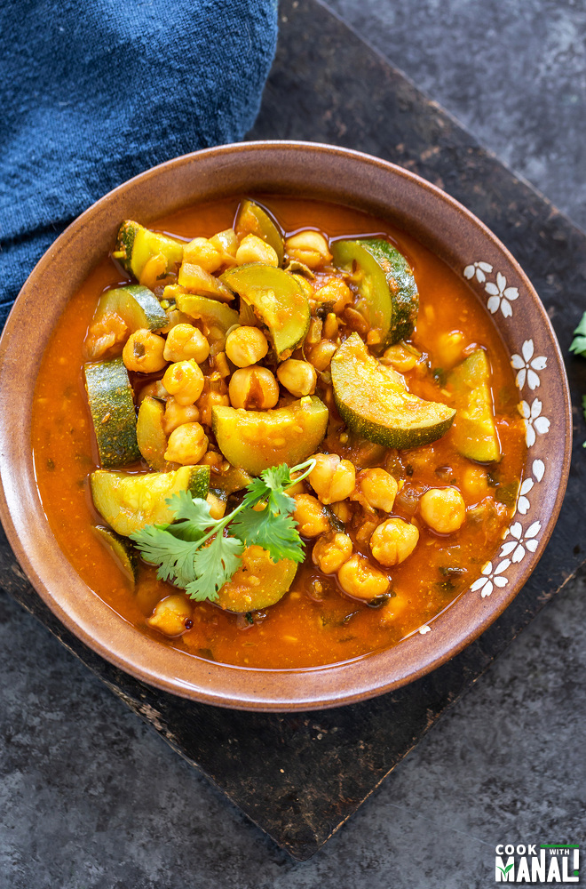 zucchini and chickpea curry served in a brow color bowl and a blue napkin placed in the background