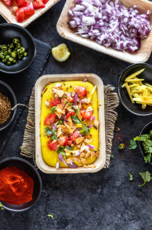moong dal chaat served in a rectangular serving bowl topped with tomatoes, onion and bowls of cilantro, chili powder, onion, tomatoes placed in the background and on the sides