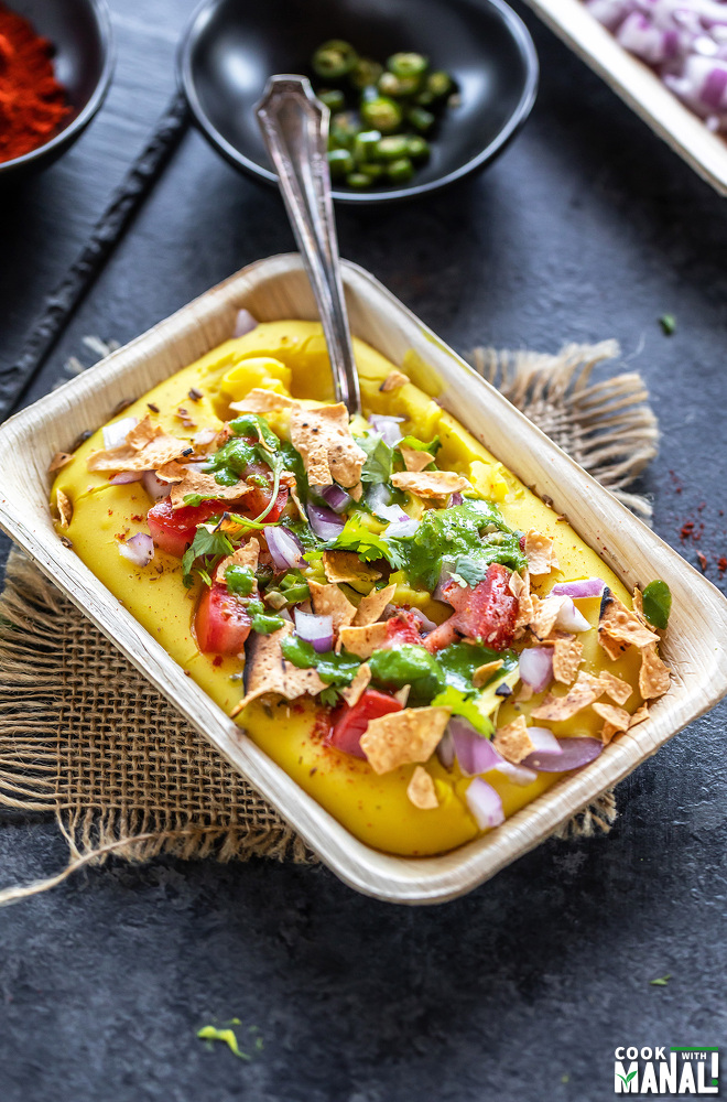 moong dal chaat served with a spoon in a rectangular bowl topped with onions, cilantro, tomatoes