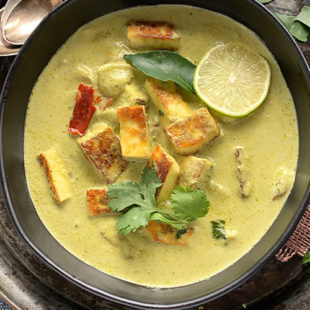 a green color curry served in a black bowl, garnished with cilantro and lime slice